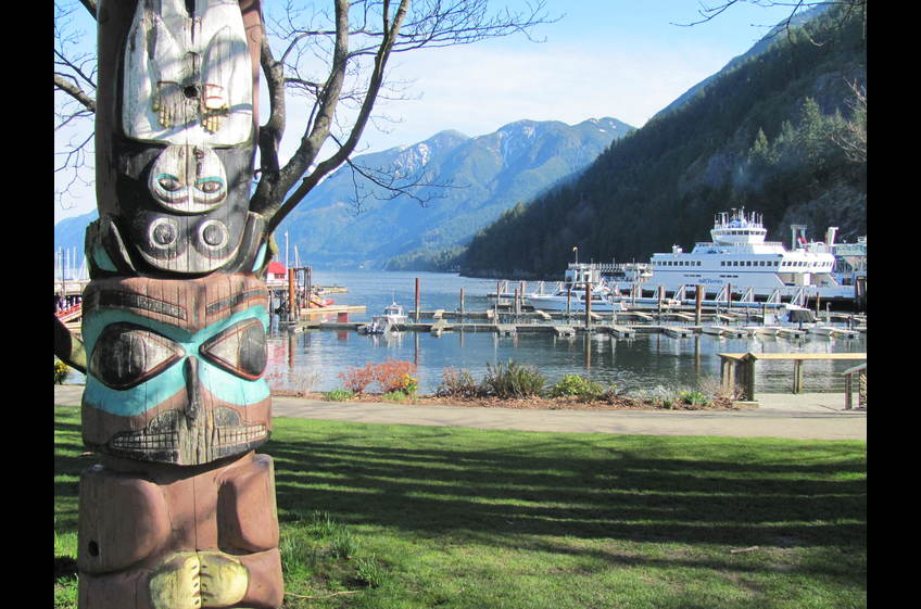 Ferry arriving  Horseshoe Bay, West Vancouver overlooked by totem pole.